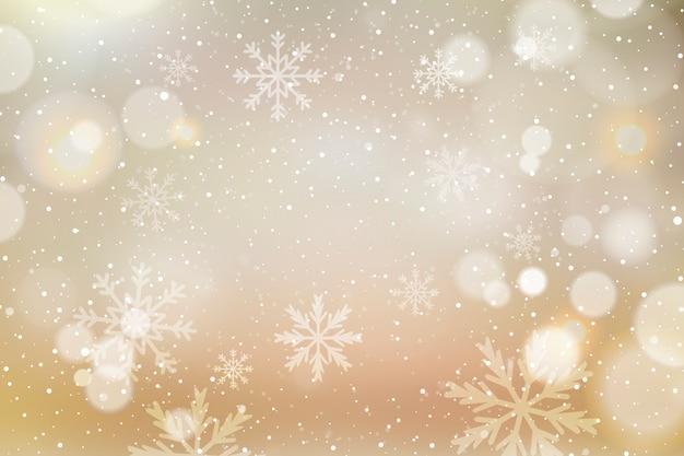 Kerstmisachtergrond met bokeh en sneeuwvlokken Gratis Vector
