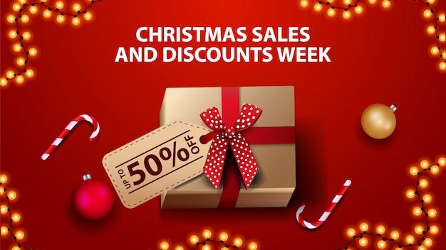Kerstmisverkoop en kortingsweek, rode banner met giftdoos, kerstmisballen en suikergoedriet, hoogste mening Premium Vector