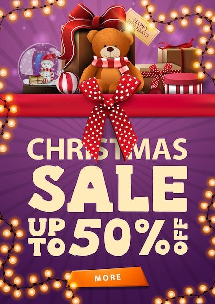 Kerstuitverkoop, paarse verticale kortingsbanner met rood horizontaal lint met strik, slinger en cadeautjes met teddybeer Premium Vector