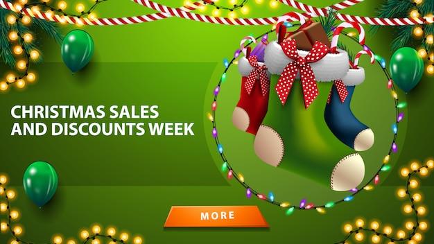 Kerstverkoop en kortingsweek, horizontale groene kortingsbanner met ballonnen, slingers, kerstkousen en knop Premium Vector