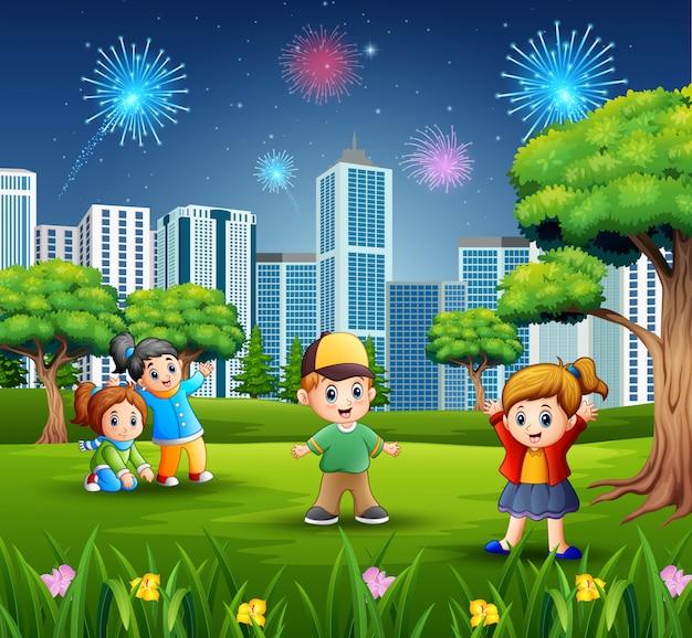 Kinderen buiten spelen met stadsgezicht en vuurwerk Premium Vector