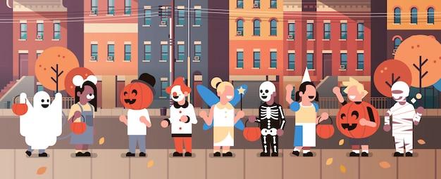 Kinderen dragen monsters kostuums wandelen stad huis gebouwen banner Premium Vector