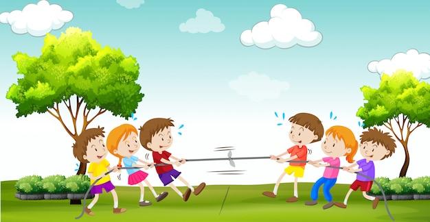 Kinderen spelen touwtrekken in het park Gratis Vector