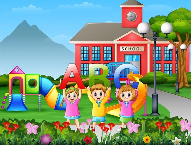 Klein kind houdt abc-brief in het schoolplein Premium Vector