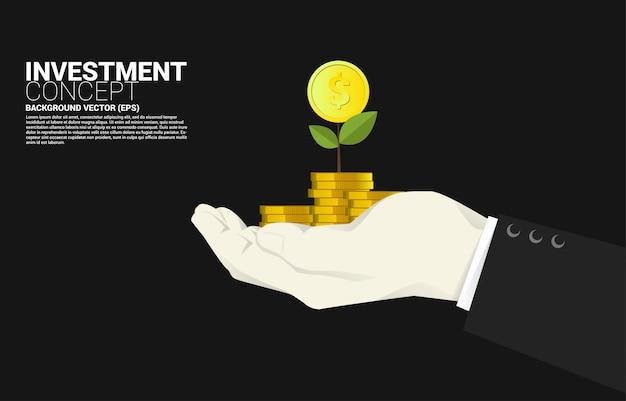 Kleine geldboom boven de dollar van het stapelmuntstuk in zakenmanhand. succesinvesteringen en groei in zaken Premium Vector