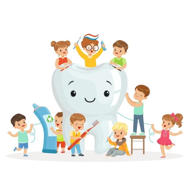 Kleine kinderen verzorgen en reinigen een grote, glimlachende tand. kleurrijke stripfiguren Premium Vector