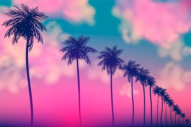 Kleurrijke achtergrond met het ontwerp van palmsilhouetten Gratis Vector