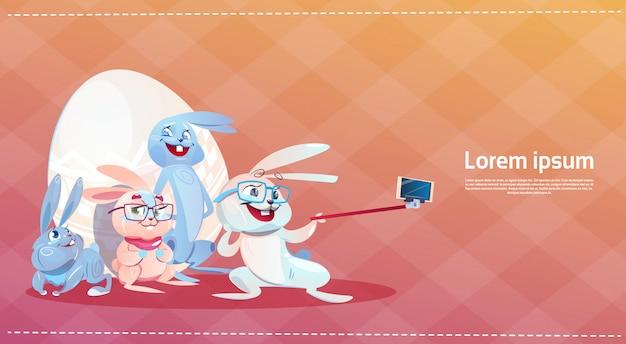 Konijn nemen selfie foto pasen vakantie bunny ingericht eieren wenskaart Premium Vector