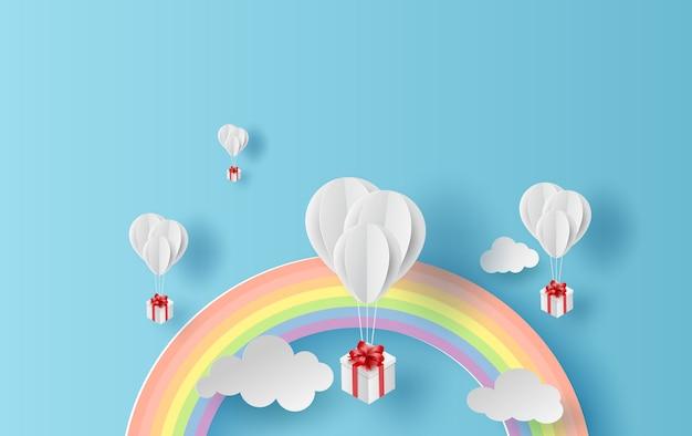 Landschap van regenboog en ballonnen op hemel Premium Vector