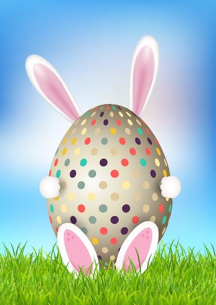 Leuke pasen-achtergrond met het ei van de konijntjesholding Gratis Vector