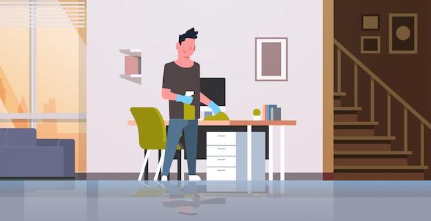 Man computer tafel schoonmaken met stofdoek man afvegen werkplek bureau huishoudelijk concept moderne woonkamer interieur mannelijke stripfiguur Premium Vector