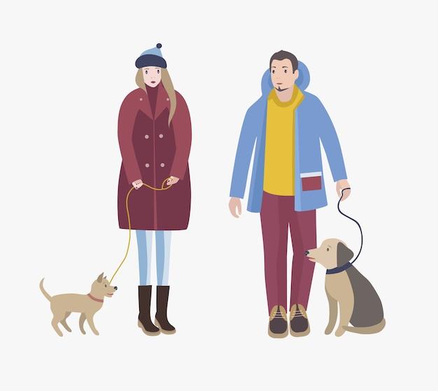 Man en vrouw gekleed in winterkleren staan, houden hun honden aan de lijn en kijken elkaar aan. stripfiguren met huisdieren geïsoleerd. gekleurde vectorillustratie. Premium Vector
