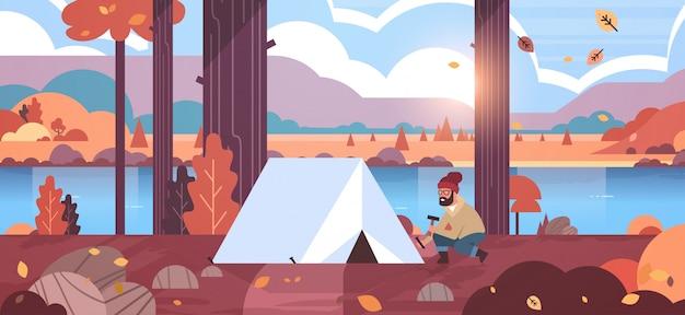 Man wandelaar camper installeren tent voorbereiden camping wandelen concept zonsopgang herfst landschap natuur rivier bergen Premium Vector