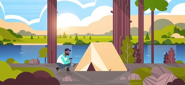 Man wandelaar camper installeren van een tent voorbereiden camping wandelen concept zonsopgang landschap natuur rivier bergen achtergrond horizontale volledige lengte Premium Vector