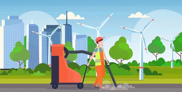 Mannelijke straat conciërge bedrijf industriële stofzuiger man stofzuigen vuilnis straten schoonmaak service concept moderne windturbines stadsgezicht achtergrond volledige lengte vlak en horizontaal Premium Vector