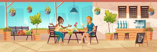 Meisjes zitten op caféterras of balkon met houten bar en planten. cartoon interieur van coffeeshop patio met tafels, stoelen en bank met slapende kat. vrouwen drinken thee en praten Gratis Vector