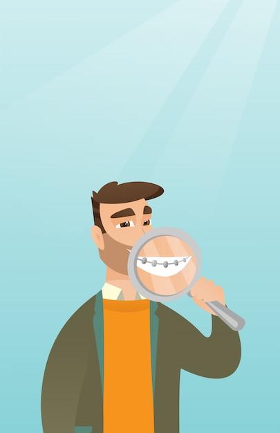 Mens die haar tanden met meer magnifier onderzoekt. Premium Vector