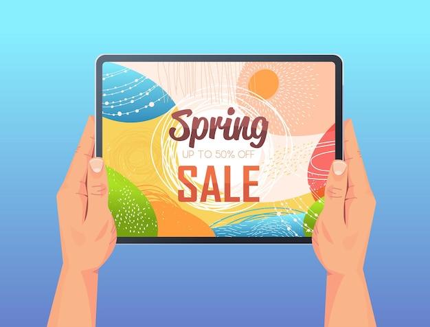 Menselijke handen met behulp van tablet pc met lente verkoop banner flyer of wenskaart op scherm horizontale afbeelding Premium Vector