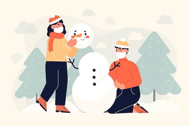 Mensen die samen een sneeuwpop maken terwijl ze gezichtsmaskers dragen Premium Vector