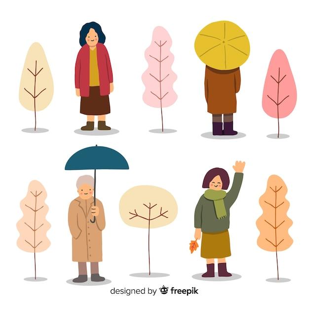 Mensen lopen in de herfstcollectio Gratis Vector