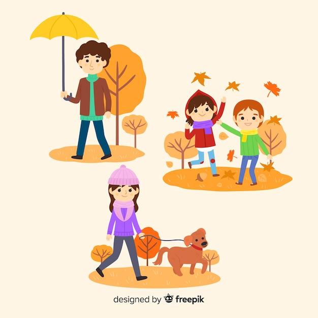 Mensen lopen in een park in de herfst Gratis Vector