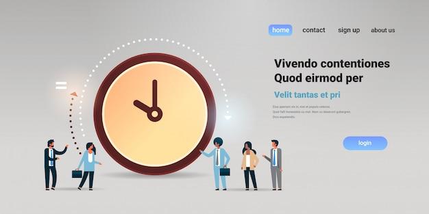 Mensen uit het bedrijfsleven communiceren in de buurt van grote klok time management deadline Premium Vector