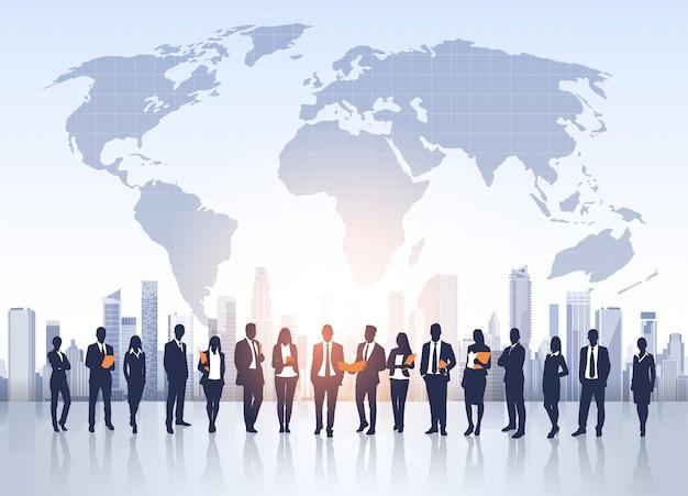 Mensen uit het bedrijfsleven groep silhouetten over stad landschap wereldkaart Premium Vector