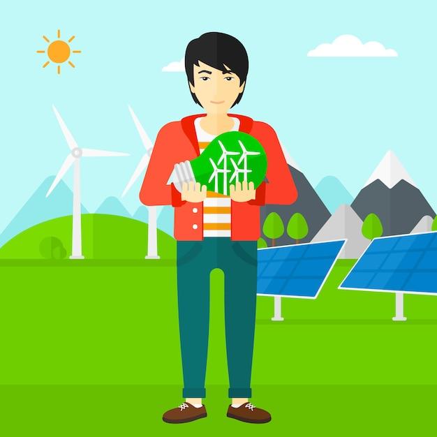 Mensenholding lightbulb met binnen windmolens Premium Vector