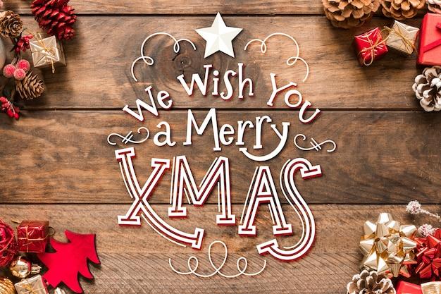 Merry christmas belettering met dennenappels en geschenken Gratis Vector