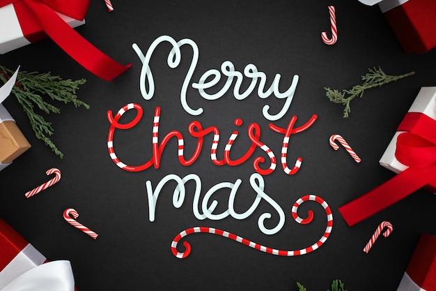 Merry christmas belettering met presenteert en snoep stokken Gratis Vector