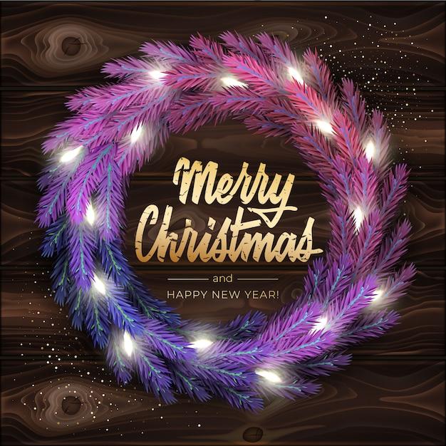 Merry christmas wenskaart met een realistische kleurrijke krans van pijnboomtakken, versierd met kerstverlichting. moderne belettering merry christmas in goud Premium Vector
