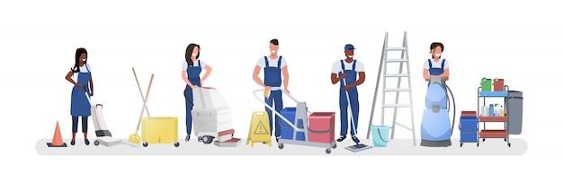 Mix race conciërges staan met reinigingsapparatuur glimlachend schoonmakers team in uniform samen te werken schoonmaak concept horizontale volledige lengte Premium Vector