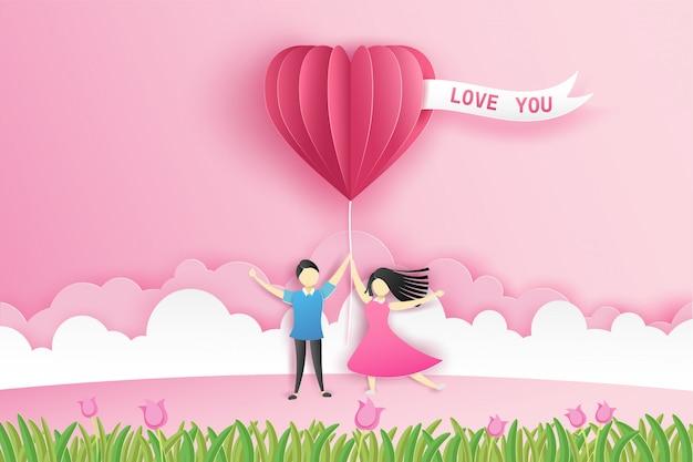 Mooi paar op de weide met origami roze ballon hart en bloemen in valentijnsdag met tekst love you. Premium Vector