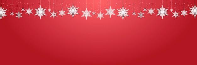 Mooie hangende sneeuwvlokken en vallende sneeuw op rood pak als achtergrond voor kerstmis, nieuwjaar en winterbanner, groetkaart Premium Vector