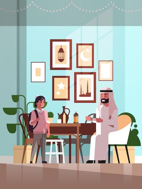 Moslim familie vieren ramadan kareem heilige maand woonkamer interieur arabische vader en zoon in traditionele kleding tijd samen doorbrengen plat verticaal volledige lengte Premium Vector