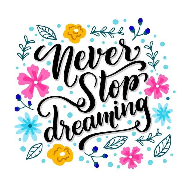 Nooit stoppen met dromen belettering met bloemen Gratis Vector
