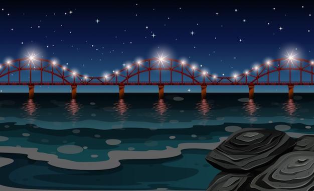 Oceaanscène met brug bij nacht Premium Vector