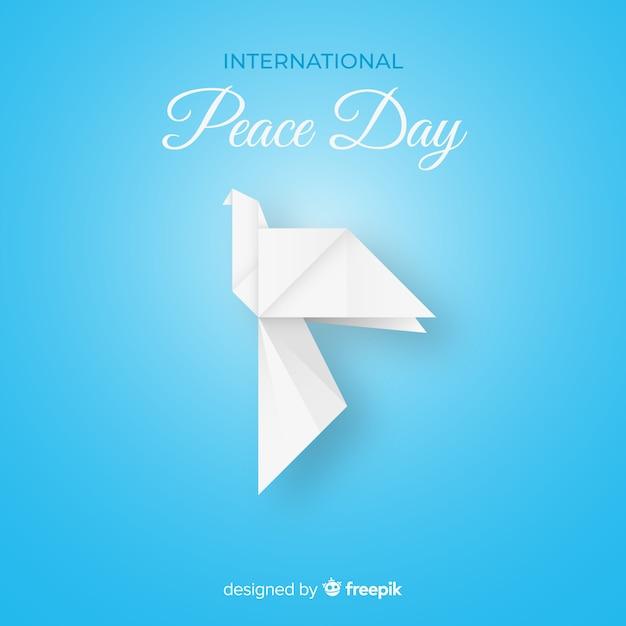 Origami witte duif op blauwe achtergrond Gratis Vector