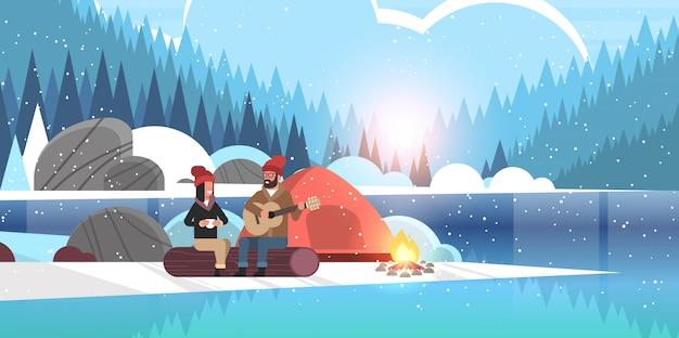 Paar toeristen wandelaars ontspannen in kamp man gitaar spelen voor vriendin zittend op log wandelen concept zonsopgang winterlandschap natuur rivier bos bergen Premium Vector