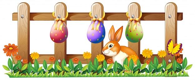 Paaseieren bij het hek en een konijntje Gratis Vector