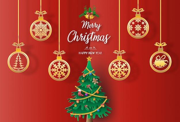 Papier kunststijl van landschap met een kerstboom en gouden kerstballen Premium Vector