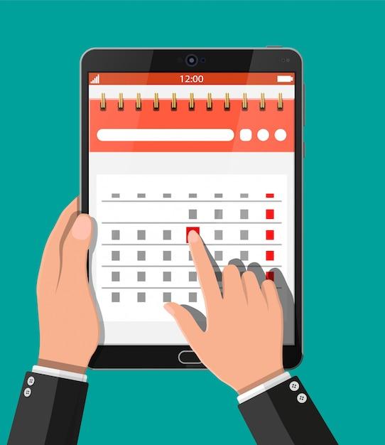 Papier spiraal wandkalender in tablet pc Premium Vector