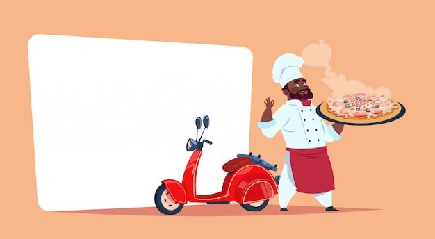Pizza levering concept african american chef-kok hold box met hete schotel permanent bij rode motor bike sjabloon banner met kopie ruimte Premium Vector
