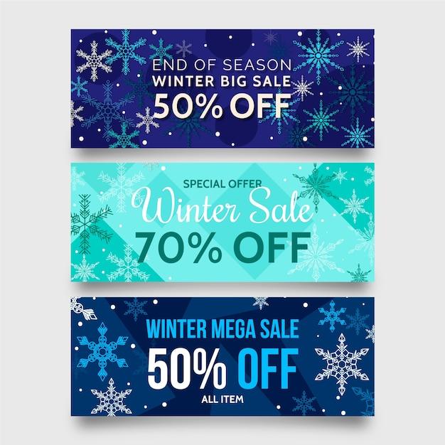 Platte winter verkoop banners met grote sneeuwvlokken Gratis Vector