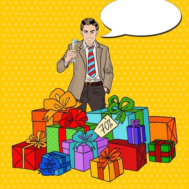 Popart gelukkig man met grote geschenkdozen en champagneglas. Premium Vector