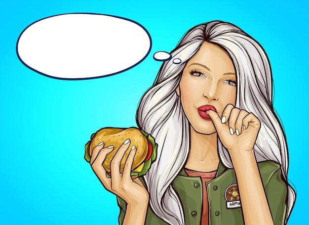 Popart meisje met hamburger likt een vinger Gratis Vector