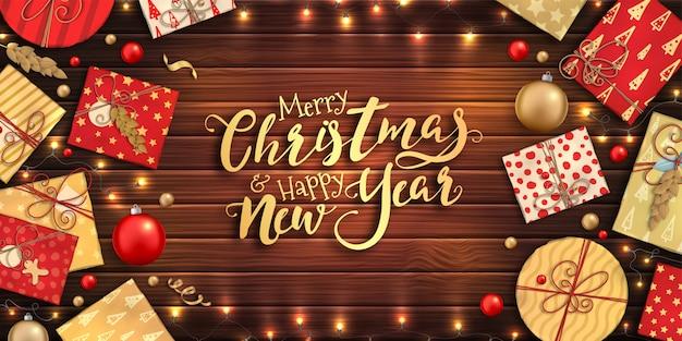 Prettige kerstdagen en gelukkig nieuwjaar poster met kleurrijke kerstballen, rode en gouden geschenkdozen, slingers op houten achtergrond Premium Vector