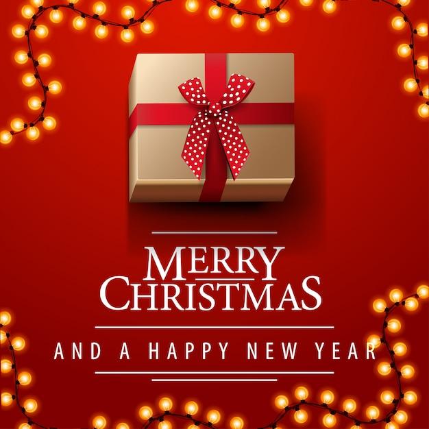 Prettige kerstdagen en gelukkig nieuwjaar rode plein ansichtkaart met garland en heden met strik Premium Vector
