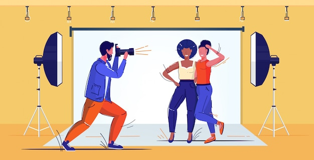 Professionele fotograaf met behulp van dslr camera man schieten mooie mix race vrouwen modellen poseren samen moderne fotostudio interieur volledige lengte schets vectorillustratie Premium Vector