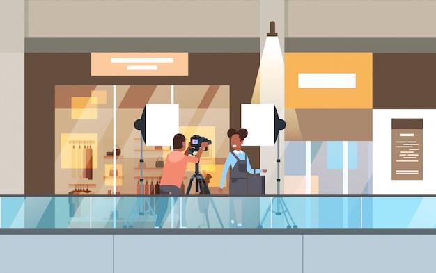 Professionele man fotograaf met behulp van dslr camera op statief schieten vrouw model meisje poseren in moderne shoping mall supermarkt interieur horizontale volledige lengte Premium Vector